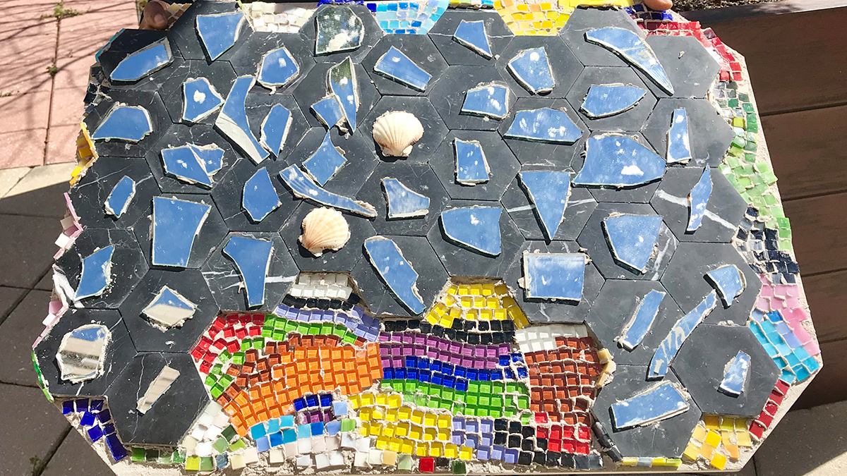 A tile work featuring glass and shells made by residents of a group home.
