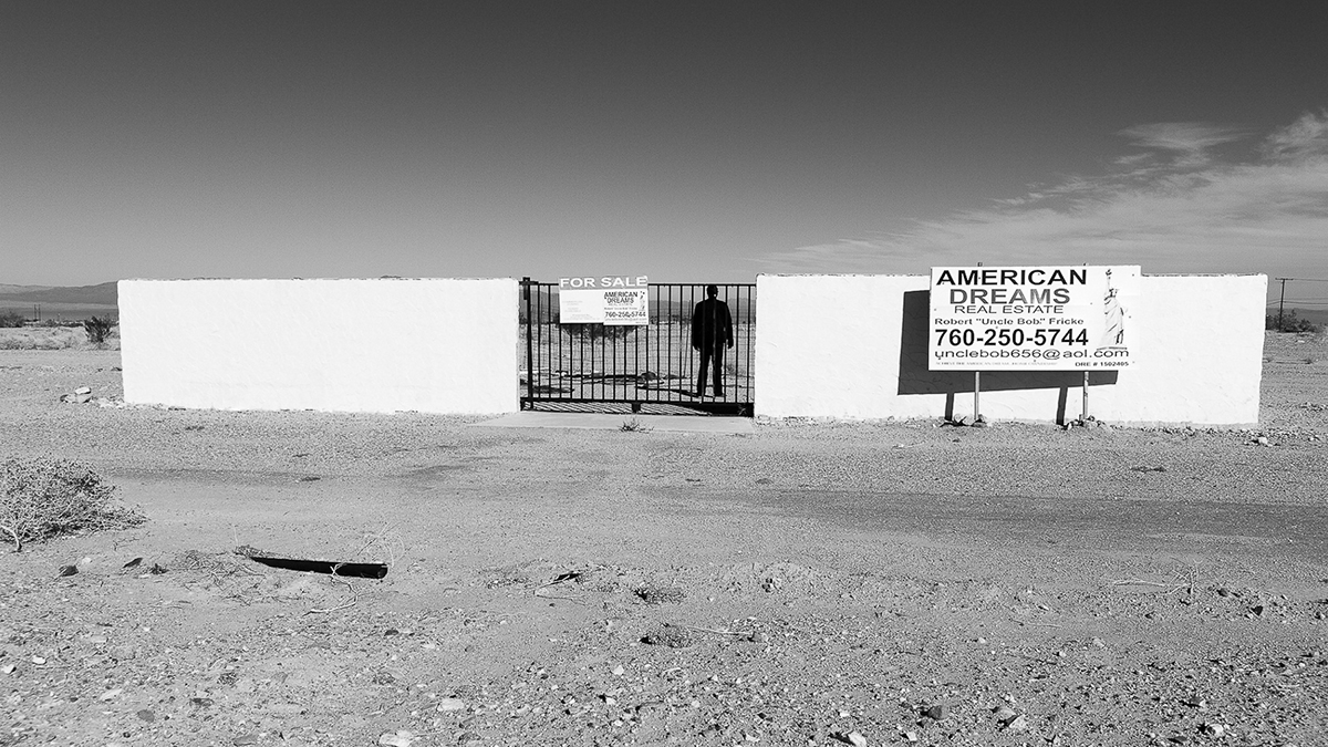 """A black-and-white photograph called Self Portrait, Sea Wind Avenue, depicting a silhouette of a man standing behind the bars of an abandoned structure in a desert with a sign that says, """"American Dreams."""""""